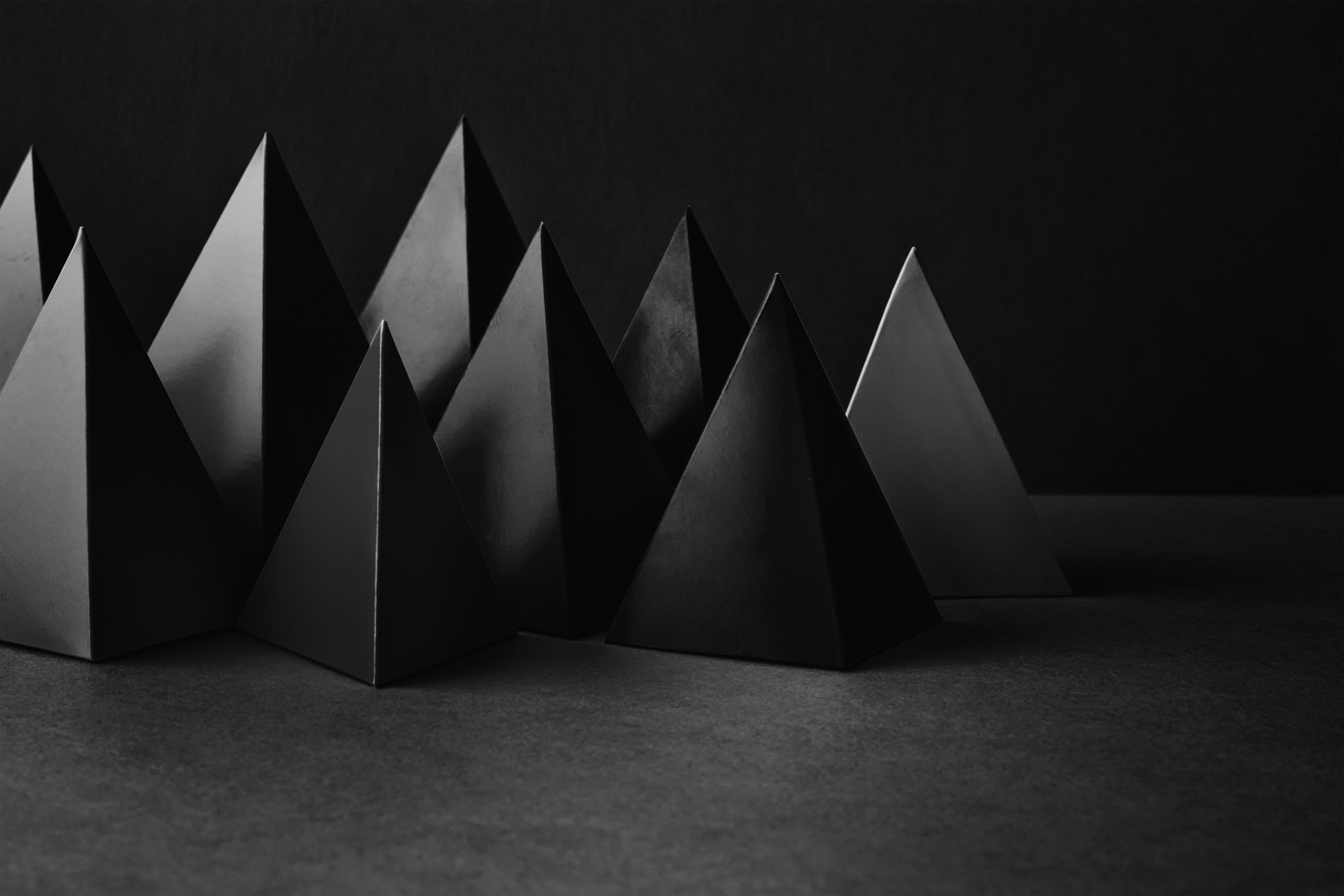 Prism pyramid objects on black gray background. Abstract geometrical figures still life composition.